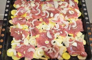 сверху на мясо выкладываем нарезанный лук