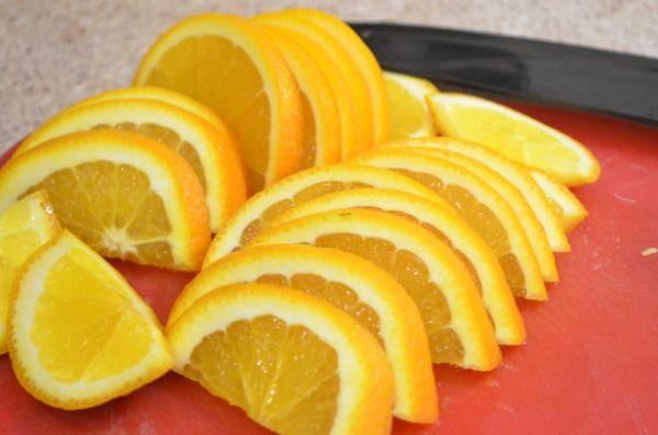 Нарезаем дольками апельсин и кладем в каждую чашку