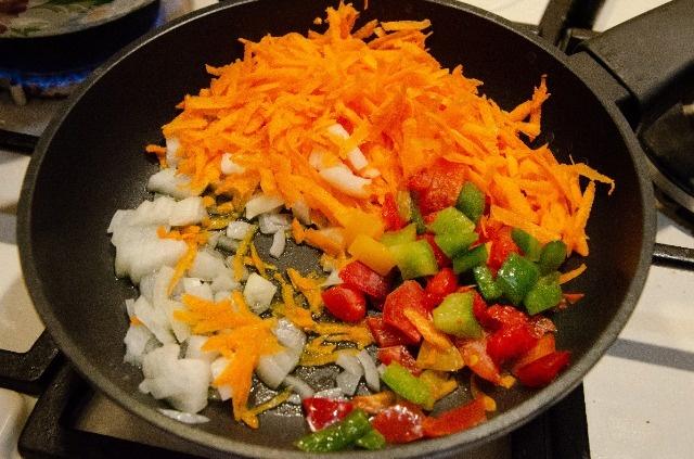 Натрите морковь на терке и добавьте к луку.